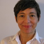 "Portraitfoto von Andrea Hofmann, dunkle kurze Haare (""Pixie-Schnitt""), dunkle Augen, lächelt"