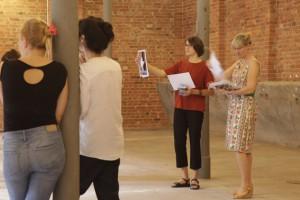 """Foto von Systemischer Aufstellung der Kunstausstellung """"Homecomings"""", zu sehen sind die zwei Kuratorinnen, die Schilder mit den Kunstwerken für die Teilnehmenden verteilen"""
