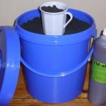 Blauer Plastikeimer mit Kohle, Tasse und Flasche mit EM