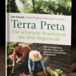 """Foto Cover Buch mit dem Titel """"Terra Preta - Die schwarze Revolution aus dem Regenwald"""", darunter Foto von einem Mann und einer Frau, die auf dunkler Erde Blumen pflanzen"""