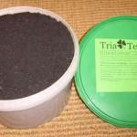 weisser Eimer mit schwarzer Kohlefüllung, daneben grüner Deckel mit TriaTerra-Beschriftung