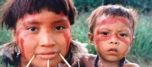foto von yanomani, ureinwohnerin regenwalt mit ihrem circa 5jährigem kind. die beiden sind im gesicht bemalt, die frau hat holzstifte im unteren teil ihres gesichtes